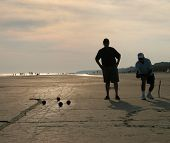 Silhouette of two men playing boccie on the beach