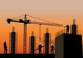 Silhouette of construction site with workers and scaffolding at sunset sky