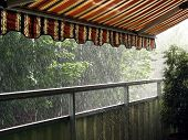 stock photo of awning  - Heavy rain in the summer time under an awning - JPG