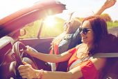 summer holidays, road trip, vacation, travel and people concept - smiling young women driving in in  poster