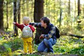 Father And His Little Son Walking During The Hiking Activities In Forest At Sunset poster