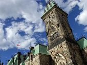 A Gothic tower stands against a partly cloudy sky at the Canadian parliament in Ottawa.