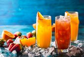 Different types of summer drinks in glasses, cubes of ice and slice of fruits  on blue table. Health poster