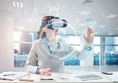 Horizontal Shot Of Beautiful And Young Business Woman In Suit Using Virtual Reality Headset With Dig poster