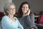 Smiling Elderly Woman And Daughter Listening To Music Together. Mother And Daughter Wearing Earphone poster