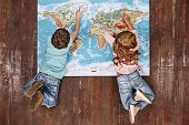 Discover The World. Children Lying On World Map, Looking At It poster