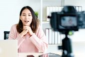 Young Attractive Asian Woman Blogger Or Vlogger Looking At Camera And Talking On Video Shooting With poster