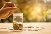 Man Hand Dropping Coin And Coins And Jar On Wooden Table In Sunlight And Blur Background Present The poster