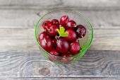 Fresh Red  Gooseberries In Glass Bowl. Fresh Wet Berries On Rustic Wooden Background. Fresh-gathered poster