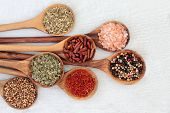 Herb and spice food seasoning in olive wood spoons with coriander seed, saffron, herbs de provence,  poster