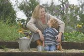 picture of happy kids  - a mother and her young son together in a flower filled garden - JPG