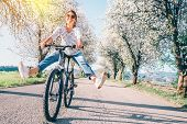 Happy Smiling Woman Cheerfully Spreads Legs On Bicycle On The Country Road Under Blossom Trees. Spri poster
