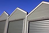stock photo of self-storage  - A row of uniform garages with roller doors on a blue sky background - JPG