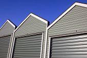 picture of roller door  - A row of uniform garages with roller doors on a blue sky background - JPG