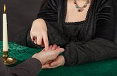 stock photo of seer  - A dark dressed woman is doing a palm reading - JPG