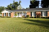 foto of residential home  - Lovely Ranch style home of red brick white trim and black shutters with an American Flag.