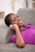 Attractive woman sitting on a couch and talking on the phone