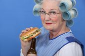 Granny eating a burger and drinking a beer