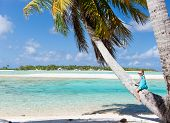 Panoramic photo of little girl sitting on coconut palm
