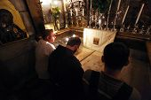 JERUSALEM - OCTOBER 01: Pilgrims pray at the tomb of Jesus in the Church of the Holy Sepulchre, traditional site of the crucifixion, burial, and resurrection of Jesus, on October 01, 2006.