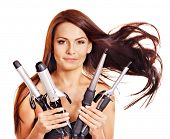 stock photo of hair curlers  - Young woman holding iron curling hair - JPG