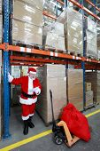 Santa claus checking list of presents in storehouse