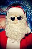 Santa Claus is listening to music in headphones. Christmas.