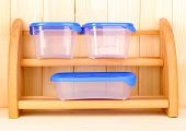 pic of tupperware  - Plastic containers for food on shelf on wooden background - JPG