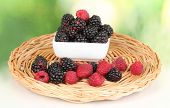 Ripe raspberries and brambles on nature background