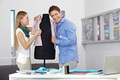 Happy man and woman in a studio dressing a dress form