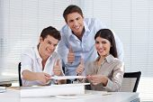 Three happy architects in their office holding the thumbs up