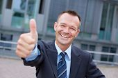 Sucessful smiling business manager holding his thumbs up
