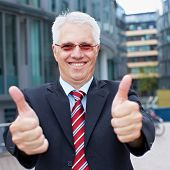 Happy senior business man holding his thumbs up outside the office