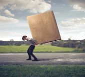 stock photo of fatigue  - Man carrying on his shoulders a large box - JPG