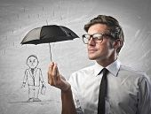 Businessman protecting with a little black umbrella a man drawn on a white wall
