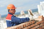 construction mason worker bricklayer installing red brick with trowel putty knife outdoors