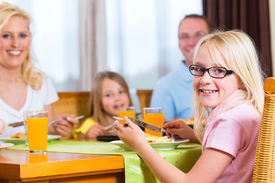 stock photo of table manners  - Family eating lunch or dinner and sitting at the table - JPG
