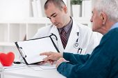 Senior man consulting with doctor and pointing at empty paper