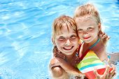 Children with armbands in swimming pool.