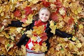 Autumn fun - lovely girl has a fun in autumn leaves, happy child