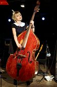 Beautiful woman in black dress plays wooden contrabass in night club.