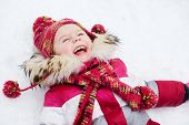 Laughing little girl lies on snow