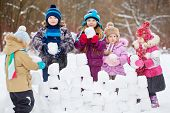 Five children build wall from snow bricks in winter park