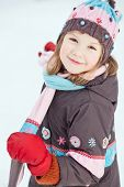 Portrait of girl wearing winter clothes against snowy background