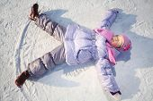 Warmly dressed little girl in pink scarf and hat lies with outstretched arms and legs on snow in winter.