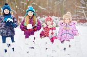 Children stand behind wall made from snow bricks holding snow blocks in their hands