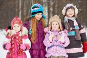 Four girls two older and two younger stands together in winter park