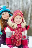 Older girl embraces her younger sister from behind sitting on snow