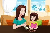 Mother And Daughter Saving Money To A Piggy Bank