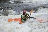 image of kayak  - Side view of a woman kayaking in rough river - JPG